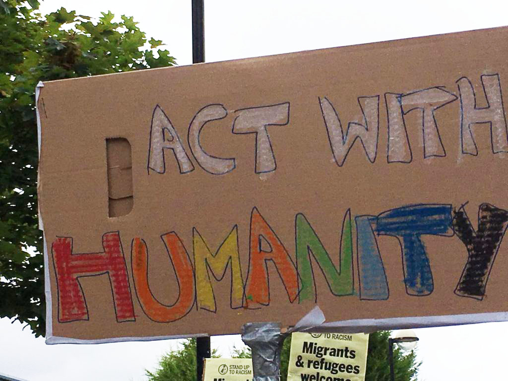 placard with the words - act with humanity